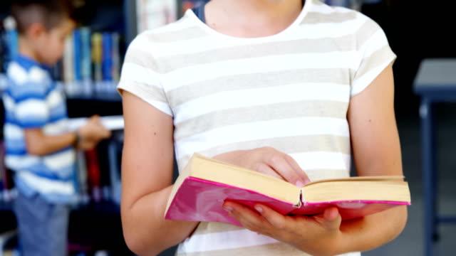 Schoolgirl reading book in library video