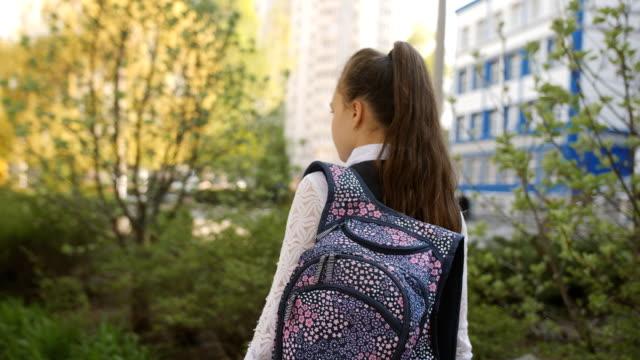 vídeos y material grabado en eventos de stock de colegiala adolescente vuelve a casa de la escuela con una mochila en los hombros. - regreso a clases