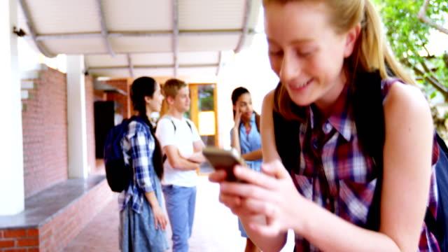 Schoolgirl using mobile phone 4k video
