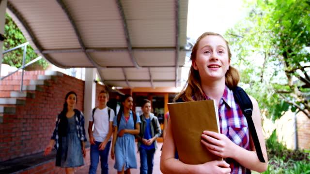 Schoolgirl waving hand while walking 4k video
