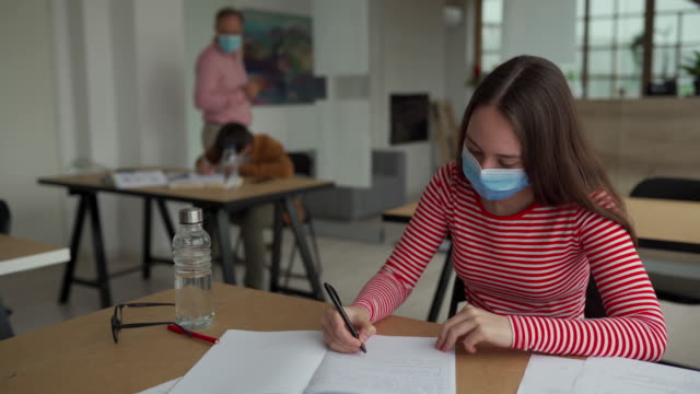 Schoolgirl with protective face mask at classroom