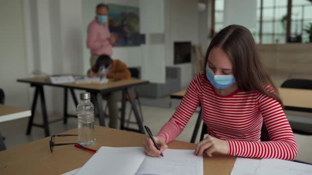 stockvideo's en b-roll-footage met schoolmeisje met beschermend gezichtsmasker bij klaslokaal - school