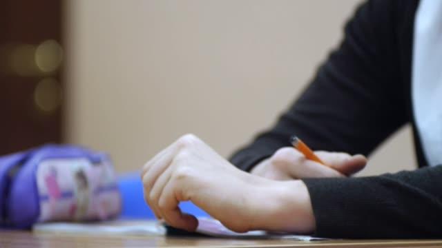 kız öğrenciler ders, öğrenmek yakın çekim eller. küçük. kalem el yakın çekim kızla - çalışma kitabı stok videoları ve detay görüntü çekimi