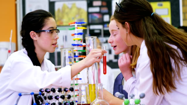 Schoolgirls smelling chemical in laboratory 4k video
