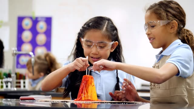 STEM schoolgirls watch for chemical reaction while creating a volcano