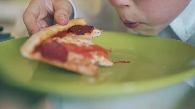 stockvideo's en b-roll-footage met schoolkid bijt pizza plak bij groene plaat in kamer close-up - dikke pizza close up