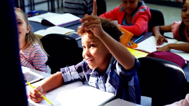 vidéos et rushes de schoolkid levant leurs mains dans la salle de classe - élève