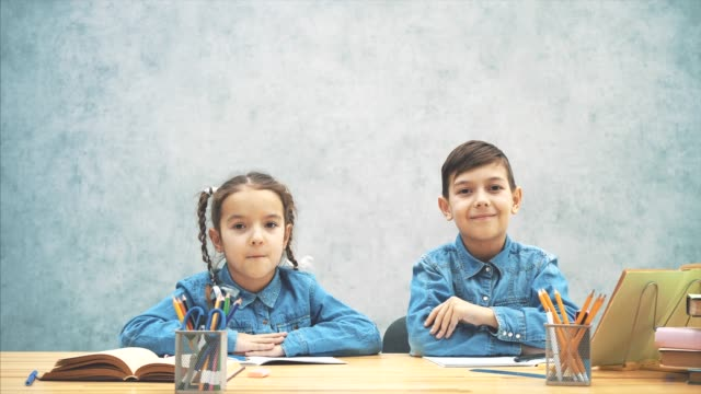 Schoolkids, brother and sister, sitting at the table, writing. Then pointing their fingers up as if they came up with an excellent idea.