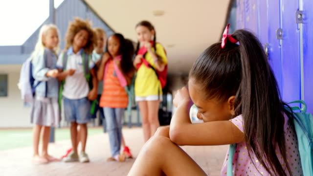 vídeos de stock e filmes b-roll de schoolkids bullying a crying asian girl in the corridor of elementary school 4k - ameaça
