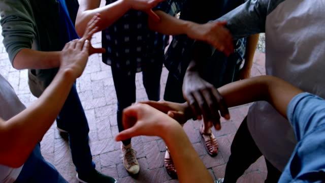 vidéos et rushes de collégiens tenant mutuellement les mains dans les locaux scolaires 4k - communion