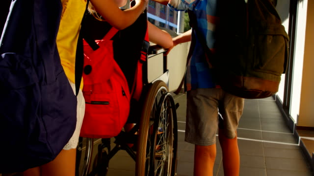 Schoolkids pushing disabled schoolgirl in wheelchair at corridor 4k Rear view of group of diverse schoolkids pushing disabled Caucasian schoolgirl in wheelchair at corridor. They are interacting with each other 4k orthopedic equipment stock videos & royalty-free footage