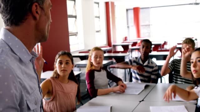 Schoolkids raising hand in classroom 4k video
