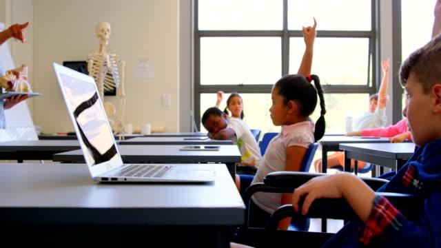vídeos y material grabado en eventos de stock de los colegiales levantando la mano mientras se sientan en el escritorio en la escuela primaria 4k - clase de ciencias
