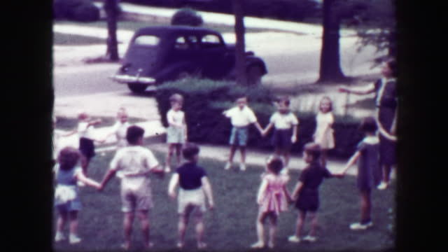 1949: Schoolmarm teacher playing Hooky Pooky childhood game in house front yard.