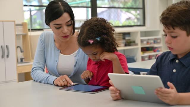 lehrer und schüler mit digitalen tablets - grundschule stock-videos und b-roll-filmmaterial