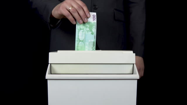 Schroeder destroys one hundred euro bill. Businessman in a suit thrusts money into a paper shredder