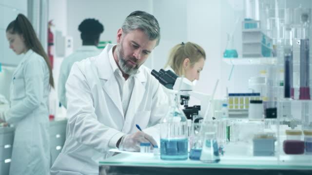 scienist schaut durch ein mikroskop - forschung stock-videos und b-roll-filmmaterial