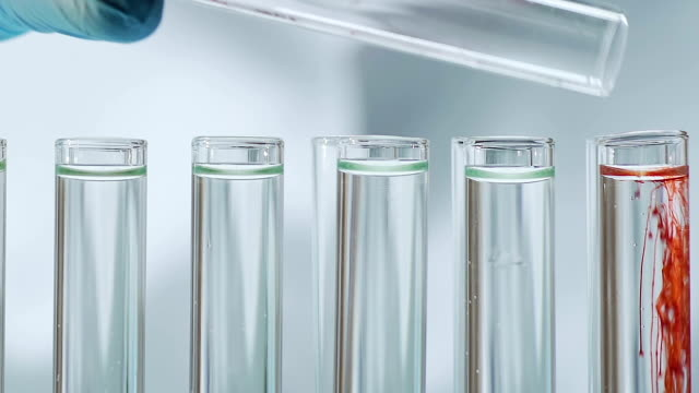 Scientist adding reagent in test tubes, conducting experiment at laboratory video