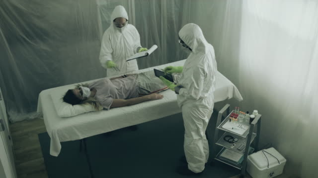 scientist attending to a woman with a virus lying on a stretcher - contagi video stock e b–roll