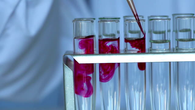 scientist consistently  adds red chemicals in water filled glass tubes - reagente video stock e b–roll