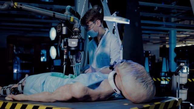 vídeos y material grabado en eventos de stock de el científico hace una autopsia de un alienígena en la sala de operaciones de una estación espacial. espacio extraterrestre tendido sobre la mesa, conectado a los instrumentos. - autopsia