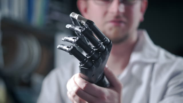 A scientist engineer is testing an electronic bionic prosthetic arm. He moves the plastic fingers of a mechanical arm. Modern technologies in prosthetics. Cybernetic hand in the hand of a scientist A scientist engineer is testing an electronic bionic prosthetic arm. He moves the plastic fingers of a mechanical arm. Modern technologies in prosthetics. Cybernetic hand in the hand of a scientist. branch plant part stock videos & royalty-free footage