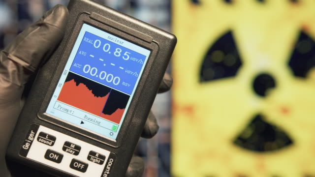 Scientist holds a Geiger counter to measure the microSieverts per hour of radiation at nuclear facility. Nuclear disaster and radiation fallout concepts.