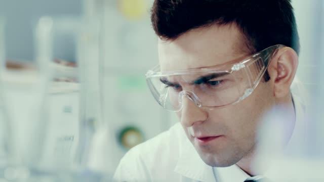 vetenskaps man i ett labb. medicinskt experiment - test tube bildbanksvideor och videomaterial från bakom kulisserna