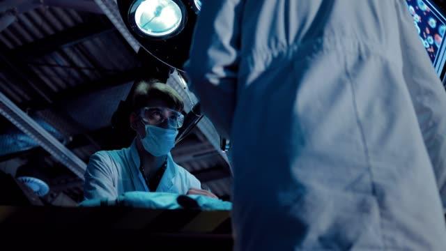 vídeos y material grabado en eventos de stock de el científico en una bata blanca y gafas lleva a cabo un experimento científico. el laboratorio está equipado con instrumentos e iluminación. vista de retrato. - autopsia