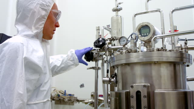 Scientist in protective suits working on vat video