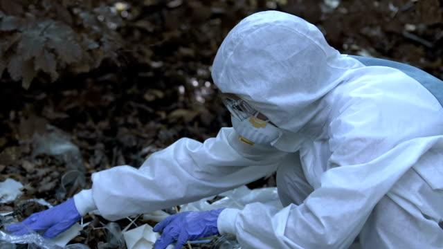 Scientist inspecting debris in forest, damage to wildlife, microplastic spread