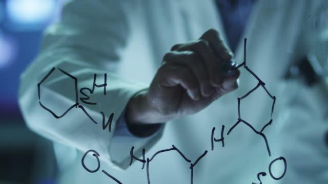 Cientista é desenho de fórmulas químicas orgânicas no vidro - vídeo