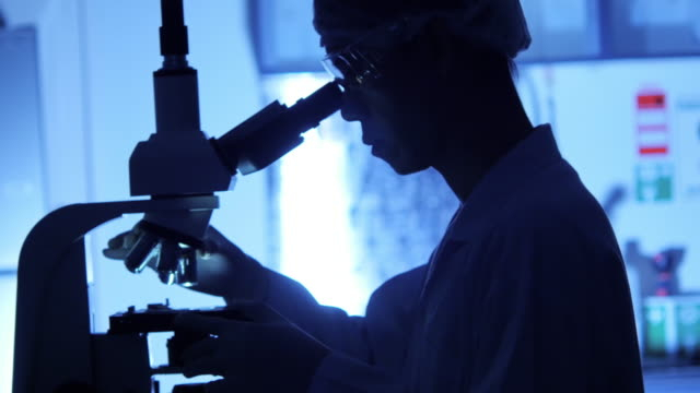 Scientist is using with microscope in dark – Video