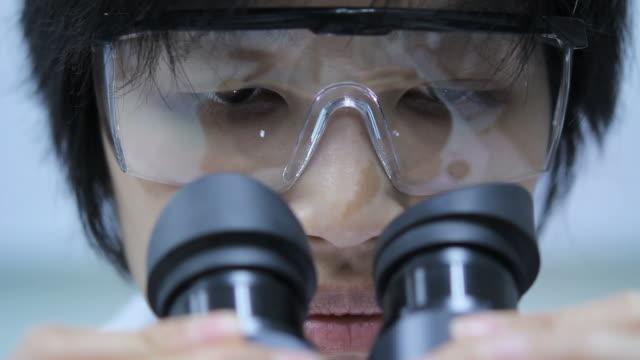 vidéos et rushes de scientifique est à l'aide de microscope - science et technologie