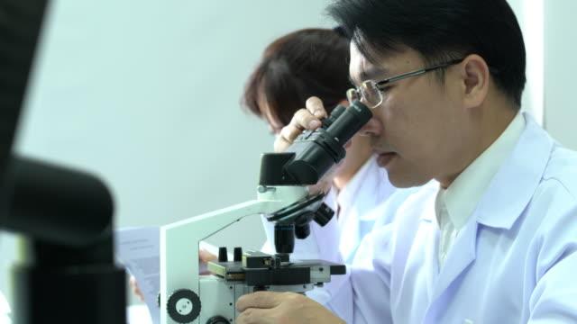 科学者の男性は現代実験室または医療センターで一緒に働く同僚と顕微鏡を探しています。テスト開発とラボの業界、科学の概念。 - 研究所点の映像素材/bロール