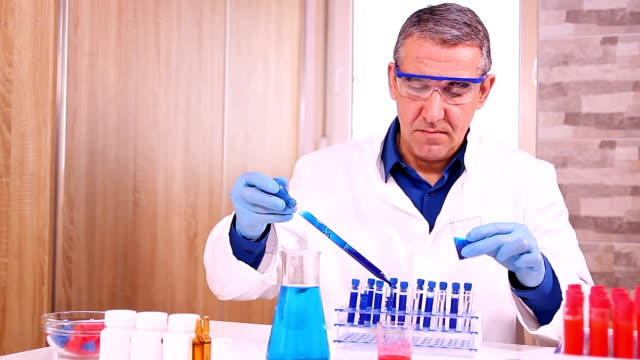 Scientist Pouring Blue Liquid with Pipette in Test Tubes video