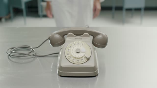 Scientist pushing away an obsolete telephone