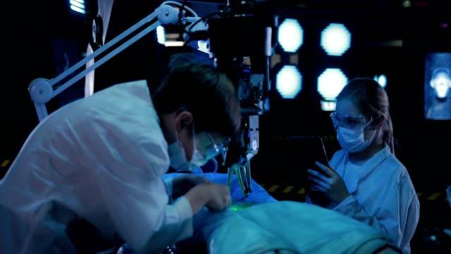 vidéos et rushes de le scientifique prend un échantillon du matériel de l'extraterrestre. il y a une autopsie d'un humanoïde dans le laboratoire. - pratique médicale