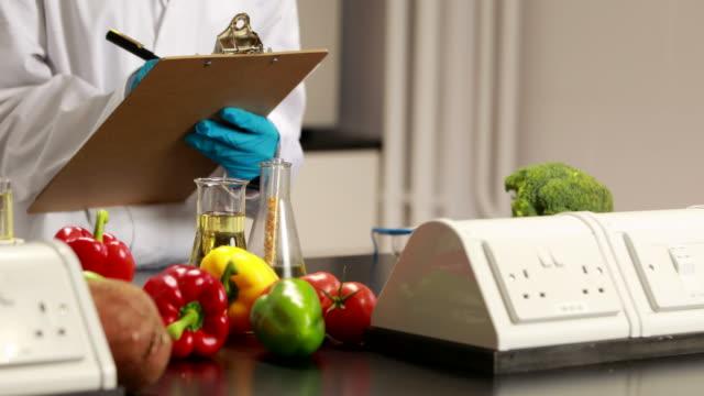 Científico tomar notas sobre el experimento de alimentos - vídeo