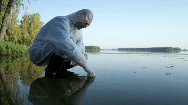 vidéos et rushes de un scientifique teste l'eau pour détecter les infections et les émissions nocives - environnement
