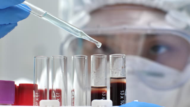 scientist transferring liquid from a pipette to a blood test tube in a laboratory