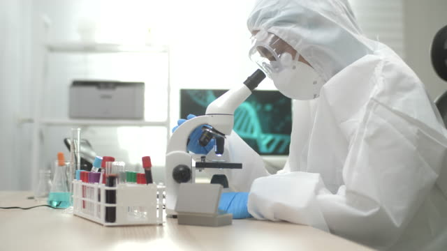 Scientist using a microscope while working inside a laboratory