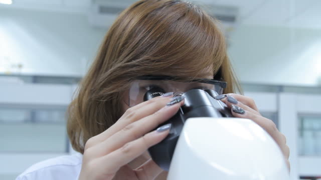 HD : Scientist using microscope video
