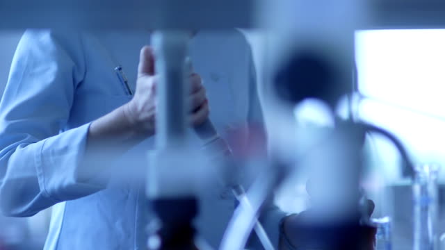 Scientist using pipette while performing experiment video