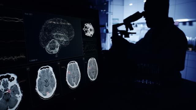 vídeos de stock e filmes b-roll de scientist with microscope. brainwave scanning research on computer screens - instrumento para diagnóstico
