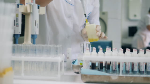 Scientist working with coronavirus samples at lab. Yellow liquid is being poured into test tubes Yellow liquid is being poured into test tubes. 4K beaker stock videos & royalty-free footage