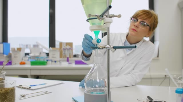 Scientist working with green turquoise liquid in separator funnel Female scientist wearing glasses and latex gloves working with green turquoise liquid in pear shaped separator funnel. Hemp seeds and cbd oils are on table. Cannabis pharmaceutical healthcare concept. cbd oil stock videos & royalty-free footage