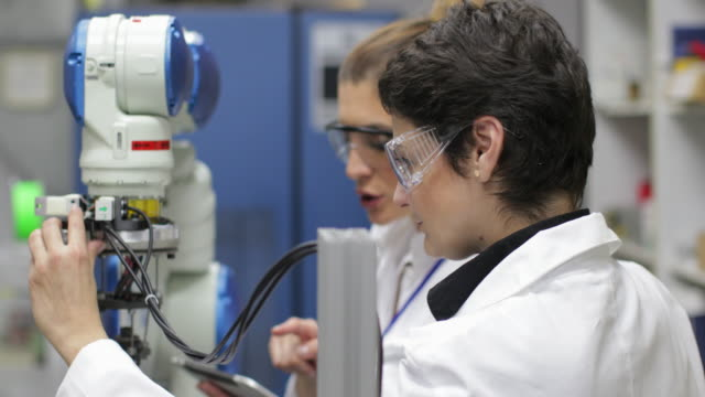 Scientist working with robotic arm Two female scientist reparing robotic arm in research lab, wearing protective eyewear, using digital tablet computer aided manufacturing stock videos & royalty-free footage