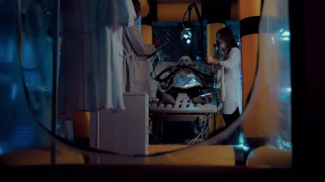 stockvideo's en b-roll-footage met wetenschappers zijn het verkennen van de alien alien, verwijder de indicatoren van de instrumenten. alien ligt in de operationele eenheid van het laboratorium, aangesloten op de observatie-apparaten. - ventilator bed