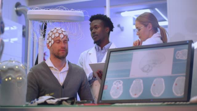 Scientists examining Brainwave Scanning Headset in laboratory.